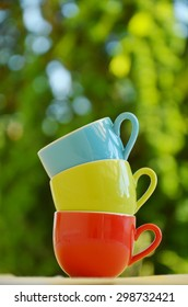 Stack of colorful mugs bokeh background  colorful Kitchenware