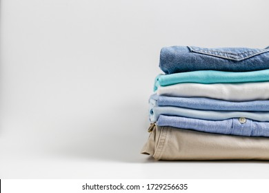 Stack of colorful perfectly folded clothing items. Pile of different pastel color shirts, sweaters isolated and other garments on white background. Close up, copy space.