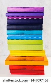 Stack of colorful rainbow books on white background