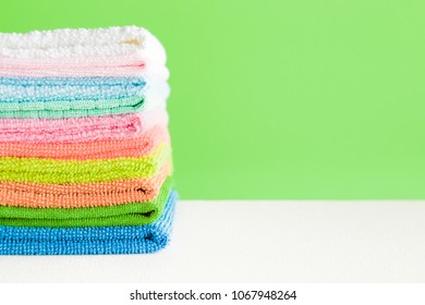 Stack of colorful, soft microfiber rags for different surfaces cleaning in kitchen, bathroom and other rooms. Towels for face and hands wiping. Empty place for text or logo on green background.