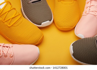 Stack of colorful sport shoes on yellow background