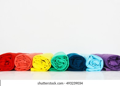 stack of colorful t-shirt rolled up on white background, copy space