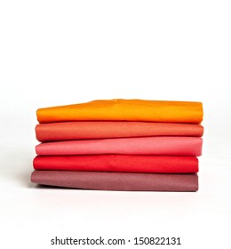 Stack of colorful t-shirts on the white background