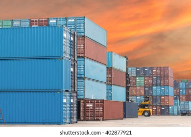 stack of containers with empty cement road in its front with sky during sunset.