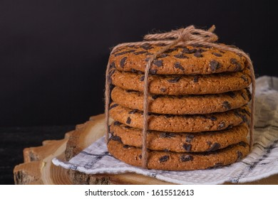 Stack of cookies with chocolate drops. Mouth-watering biscuits on a towel and a piece of wood. Food concept.