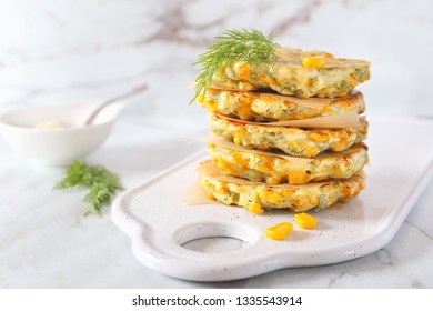 Stack of corn pancakes with sauce on light background