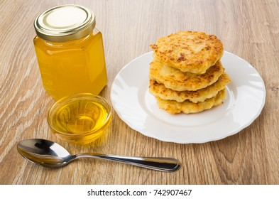 Stack of cottage cheese pancakes in plate, bowl and jar of honey, teaspoon on wooden table