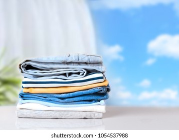 Stack cotton clothes on white table empty space background.