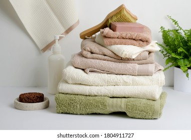 A stack of COTTON TOWELS brown, cream and Colours on a white background. This composition is great for CPA treatments and relaxation. Copy space