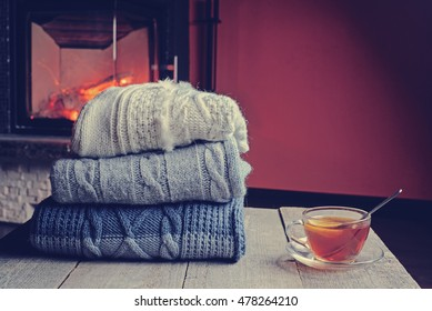 Stack of cozy knitted sweaters and cup of hot tea with lemon on old wooden table, near burning fireplace  at background. copy space