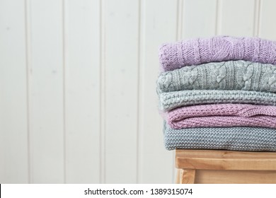 Stack of cozy knitted sweaters on a wooden ladder. Scandinavian style. White wooden wall