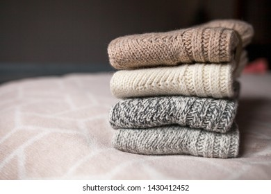 Stack of cozy knitted wool clothes on the bed. Retro style. Warm comfortable concept. Handmade work.