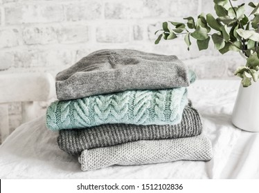 Stack of cozy winter autumn sweaters pullovers on the table on a light background