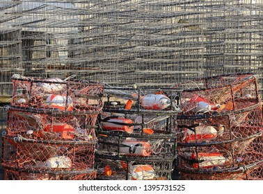 A stack of crab traps loaded with colorful buoys and line sit waiting for the beginning of crab season, with a stack of metal unloaded traps in the background