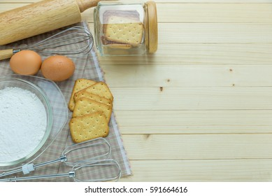 Stack of Crackers on white ceramic dish and ingredients,kitchenware on wooden table.