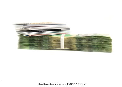 Stack of credit cards on top stack of green bills isolated on white background