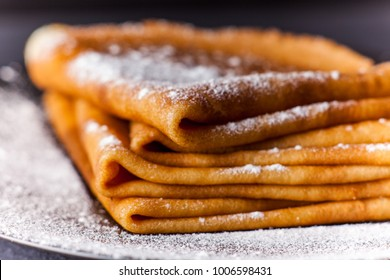 Stack of crepes with powdered sugar on dark background. Pancakes for breakfast