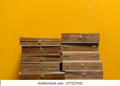 A stack of Cuban cigar boxes in front of a yellow wall.