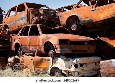 Stack of damaged rusted car scraps on junkyard