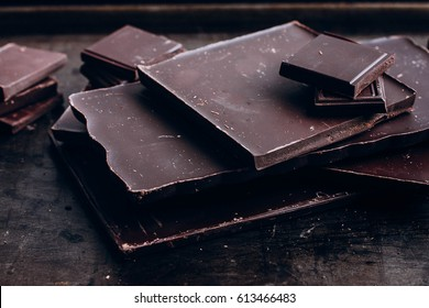 Stack of dark chocolate  on wooden table background. Sweet food. Copy space, top view
