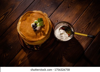 a stack of delicious freshly fried pancakes on a clay plate with sour cream and currant berries, next to it sour cream in a wooden bowl