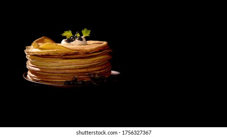 a stack of delicious freshly fried pancakes on a clay plate with sour cream and currant berries