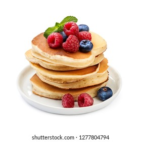 Stack of delicious pancakes with berries and mint leaf on plate isolated on white.