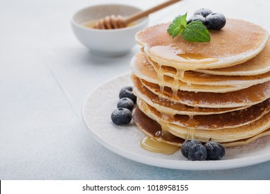 A stack of delicious pancakes with honey and blueberries on a light blue background. with copy space
