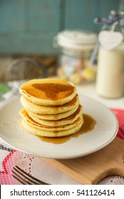 Stack of delicious pancakes with maple syrup on plate and napkin on wooden background