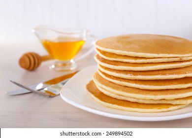 Stack of delicious pancakes on plate with honey in saucer on table and light background