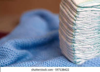 Stack of diapers or nappies on blue knitted blanket, closeup.