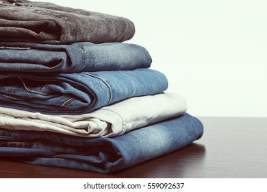 Stack of different aged folded jeans on wooden table. Low aperture shot, focus on front part, vintage tone