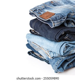 Stack of different blue jeans on white background