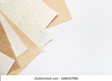 Stack of different handmade paper on a white background