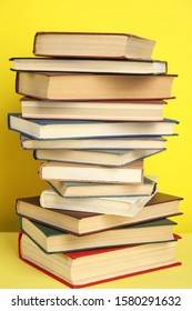 Stack of different hardcover books on yellow background