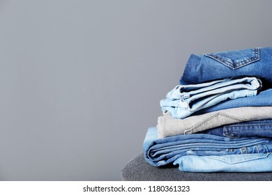 Stack of different jeans on stool against gray background. Space for text