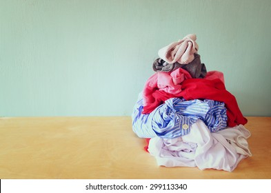 stack of dirty clothes for laundry over wooden table. house choirs concept
