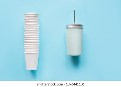 Stack of disposable white cups weekly use and counterweight reusable mug for drinks daily use on blue background. Zero waste. Waste free planet.