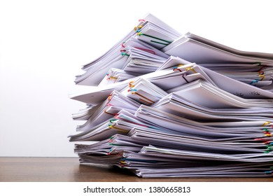 Stack of document paper with colorful paperclip place on wooden table, business concept paperless used and work overload .