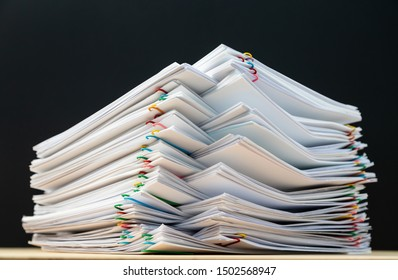 Stack of document paper with colorful paperclip place on wooden table and black ground, business concept footage paperless used.