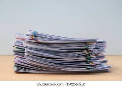 Stack of document paper with colorful paperclip place on wooden table, business concept footage paperless used.