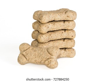 Stack of dog treats, biscuits, or snacks with white background.
