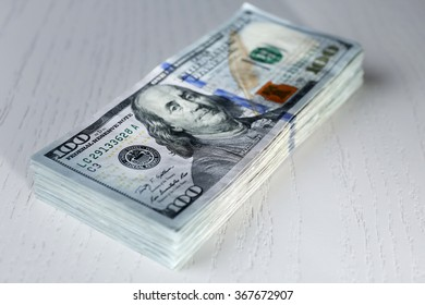 Stack of dollar banknotes on light wooden background