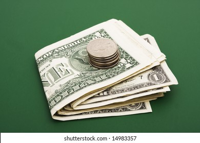 Stack of dollar bills with coins on a green background