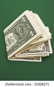 Stack of dollar bills on a green background