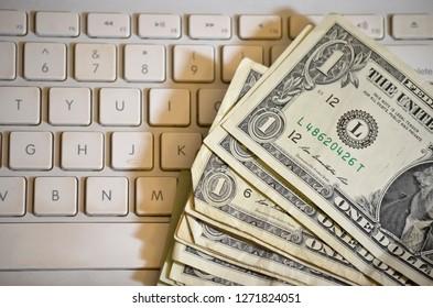 Stack of Dollar Bills on Laptop Keyboard