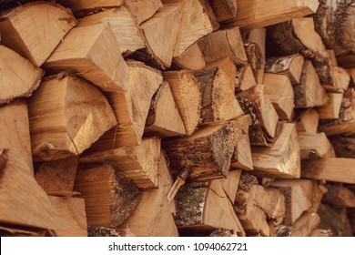 A stack of dry firewood, prepared for winter. Material for heating the house. Ecological natural fuel. Firewood texture for the background.