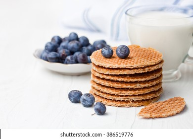 Stack  of Dutch caramel waffles with blueberry and cup of milk