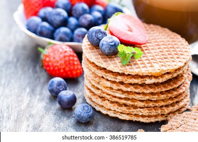 Stack  of Dutch caramel waffles with blueberry and strawberry with cup of coffee