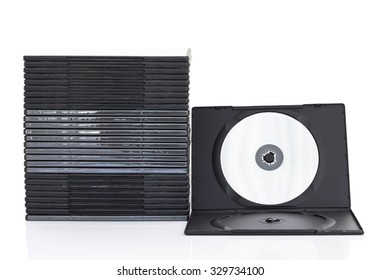 Stack of dvd boxes with disc on white background